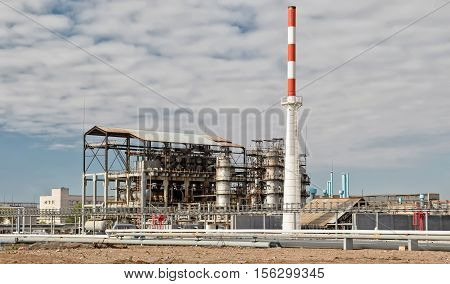 Old installation of a refinery smokestack under cloudy sky