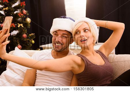 Picture of happy Christmas couple making self photos on mobile or smart home while celebraring New Year or Christmas at home