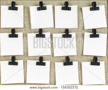 Notice board with twelve clips and blank note paper. Empty space for more text on each square.