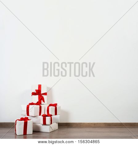 A pile of Christmas gifts in colorful wrapping with ribbons against the wall on a beautiful hardwood floor with copyspace.