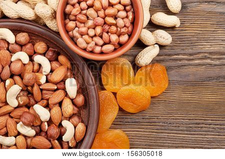 Different nuts and dried fruits on a wooden table. Almond hazelnut peanuts and cashew. Background with nuts and dried apricots.
