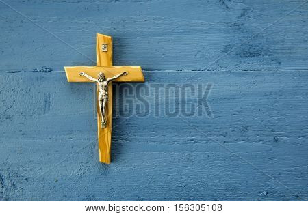 Catholic cross on a blue wooden background