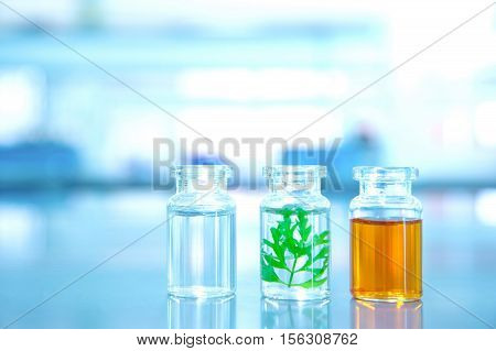 three clear vial with green leaf water and orange solution in lab science background