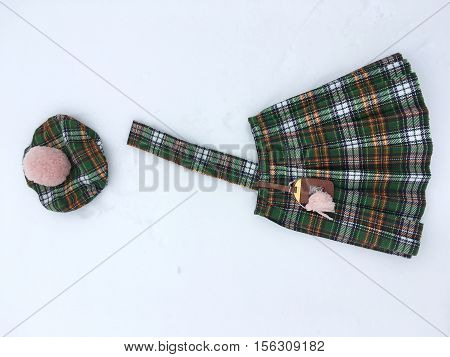 costume in Scottish style, green, brown plaid, the costume consists of skirt with pleats and hanging on belt bag with tassel, beret with pompom pale pink