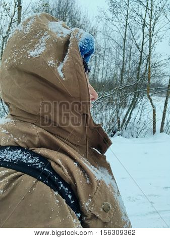 walking in the winter under the snow, the snow had obscured the dozens of jacket, hood and shoulders, view profile, lots of snow around