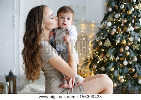 Happy brunette woman with long hair,dressed in a short beige dress,conducts the new year's holiday sitting on a white sofa near the festive Christmas tree with their little son in her arms,Christmas portrait of a mother and child