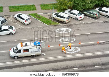 MOSCOW RUSSIA - September 24.2016: Brigade of platelayers inflict the signs of limitation of speed of cars on the asphalt of road