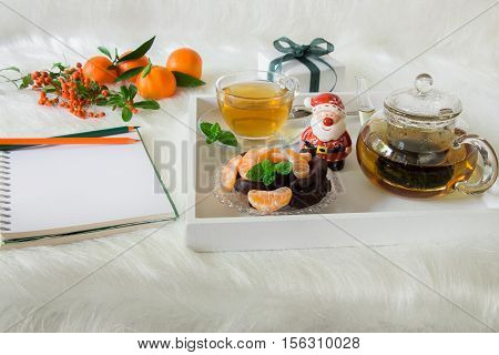 Green mint tea, chocolate, mandarin slices and Santa Claus on tray near notebook, pencils, mandarins, mountain ash on white artificial fur background. Time break notebook surprise preparation.