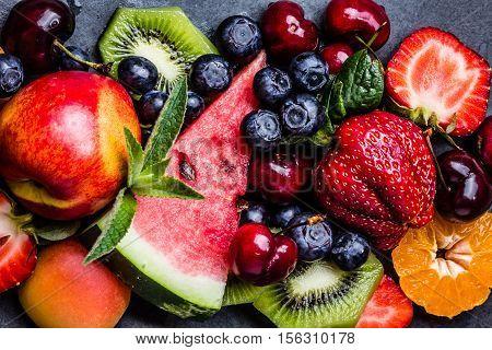 Assortment of summer fresh berries and fruits. Mix of blueberry, cherry, kiwi watermelon, strawberry, tangerine, mandarin peach, clementine on black slate plate on black slate plate. Top view