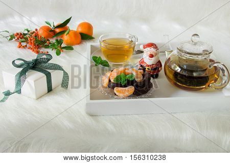 Green mint tea, mandarin slices, chocolate and Santa Claus statuette on tray near gift box, mandarins, mountain ash on white artificial fur background. Happy winter day with mint tea, dessert, gift.