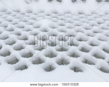 surface with many square holes, photographed so that they became similar to diamond, the whole surface is covered with snow