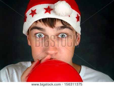 Teenager in Santa's Hat inflate a Red Balloon