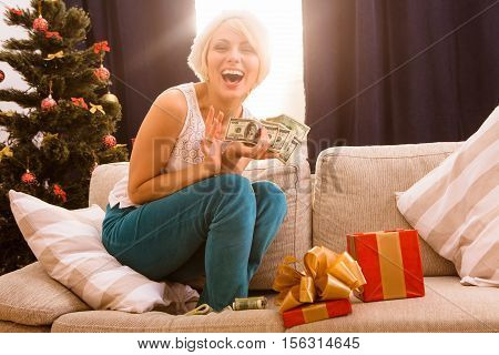 Hppy smiling and laughing Christmas woman holding money dollars given as New Year gift or present by Santa Clause or husband. New Year or Christmas concept.