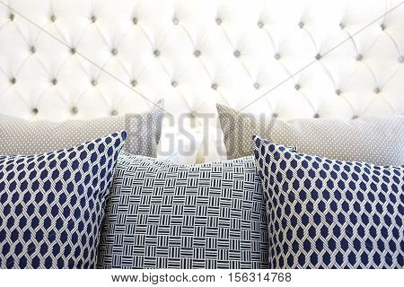 pillows on modern black and white bed in bedroom at home.