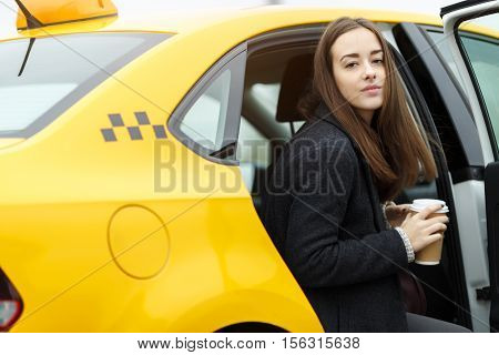 Young business woman sitting in the backseat of yellow taxi and holding coffee