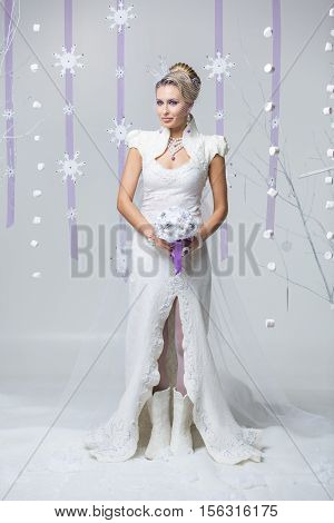 Beautiful young woman in wedding felting dress and boots holding crystal flowers bouquet. Gorgeous winter bride with bright purple make-up and fancy hairdo Standing on snow flakes background. Copy space.