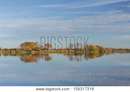 A calm reflective lake in the fall.