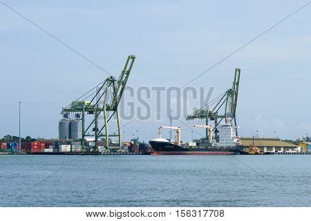 Muara,Brunei-Nov 10,2016:Container cargo ship with working crane loading bridge at Muara port,Brunei.Muara Port,which is Brunei Darussalam main port and the Gateway for Trade.