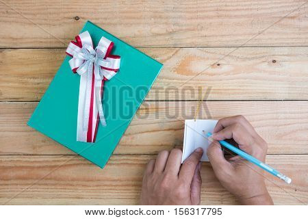 Man writting in a card.Green gift box ribbon red and silver on the table with coffee mugs and greeting cards.