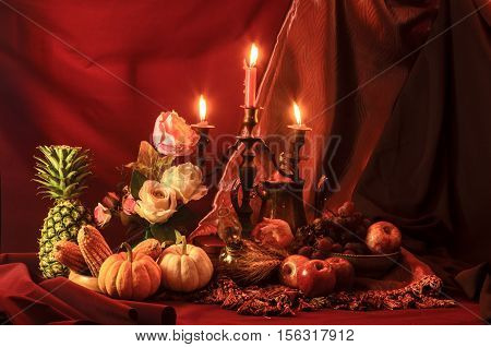 Still life with candle fruits and rose on red tone background.