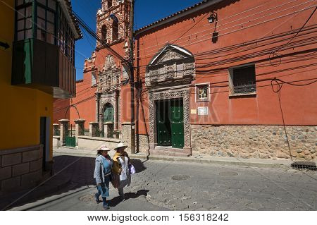 Potosi Bolivia - November 29 2013: Two women wearing traditional clothes in the city of Potosi in Bolivia. Potosi is one of the highest cities in the world and it was the major supply of silver for Spain during the colonial era.