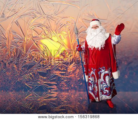 Bright winter sun shining through abstract frost patterns on the window. Santa Claus waving his hand and wish you a happy Christmas.