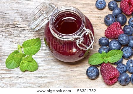 Raspberry marmalade and the fresh raspberries and blueberries on a wooden background