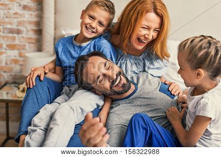 Family life is about fun. young smiling family of four having fun while lying on bed and hugging each other