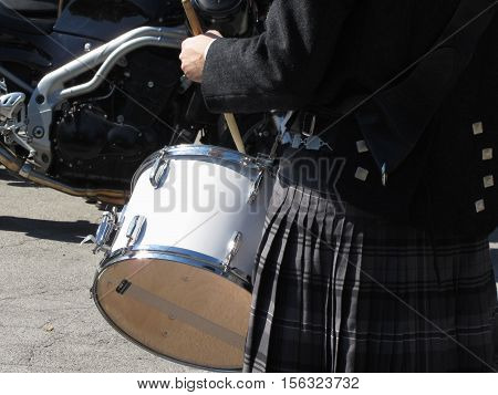Man with kilt playing on drums . Closeup of motorcycle for background
