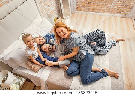 Fun for whole family. Top view shot of happy smiling family having fun while lying on bed, carrying out their weekend