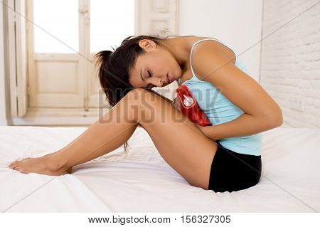 young beautiful hispanic woman in painful expression holding hot water bottle against belly suffering menstrual period pain lying sad on home bed having tummy cramp in female health concept