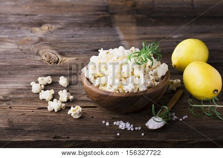 Salty crunchy fresh homemade popcorn flavored with lemon peel and rosemary scent in a wooden bowl on a simple wooden background. The concept of natural homemade organic seasonal food. selective focus