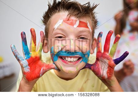Portrait of a cute happy boy showing his hands painted in bright colors