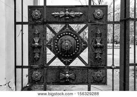 Wrought iron gates of the park. Decorative elements. Black and white photo.