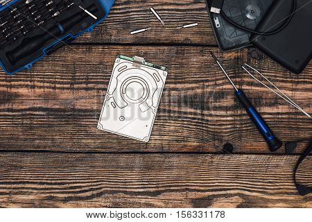 HDD with Screwdriver and Other Tools on Wooden Table