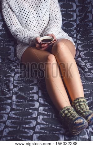 Detail of sexy young woman. Woman keep a coffee cup and read a book. She is sitting on a blanket.. Naked legs. Home atmosphere.