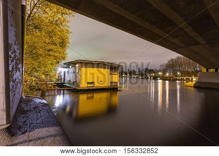 Night scene of a houseboat situated under a bridge in the Amstel river in Amsterdam, Netherlands