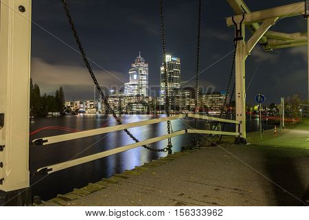 Traditional Dutch drawbridge along the Amstel river in the Amsterdam city center. Night scene with the Breitner Mondriaan and Rembrandt tower in the background. Red light trail shows path of a jogger.