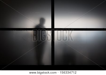 Silhouette Of Man Behind Matted Glass