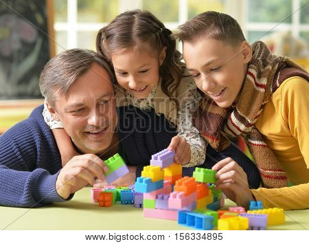 Portrait of happy father with kids play lego game together poster