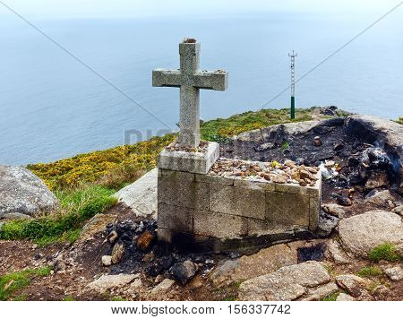 Cross and fireplace (where in tradition travelers burned some of their clothes at the end of the way and leave wishes) on cape Fisterra (Galicia Spain). Summer foggy weather.