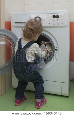 small child puts laundry in the washing machine in the bathroom