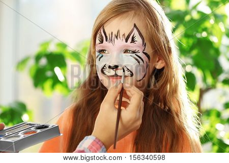 Master making aqua makeup on girl face