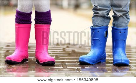 Close up view of children legs in gumboots standing on wet pavement