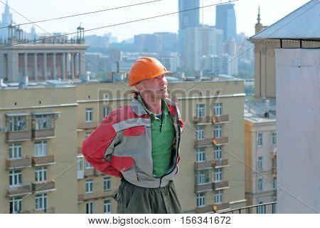 Man builder in uniform on the roof. City background