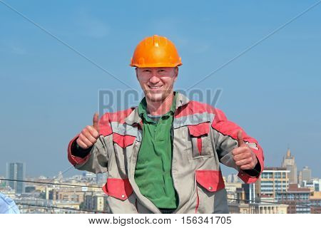 Smiling man builder show thumb up on the roof. City background