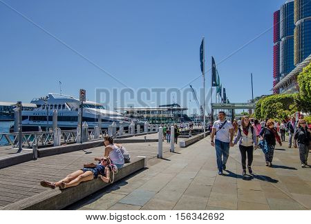SIDNEY - AUSTRALIA NOVEMBER 2, 2016: People walk along the promenade at Darling Harbour, one of the city's largest dining, shopping and entertainment districts and a popular destination for visitors.