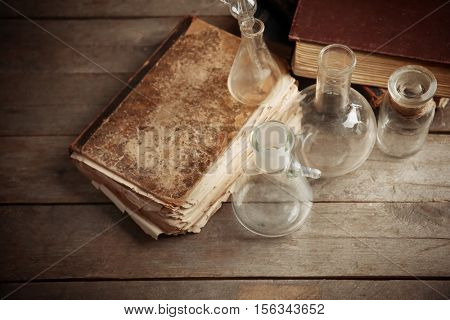 Glass flasks and old books on wooden background, closeup