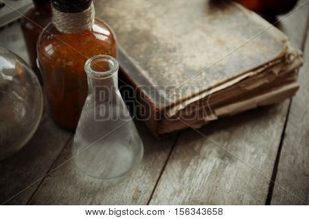 Vintage equipment of chemical laboratory on wooden background, closeup
