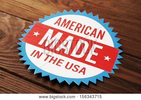 Tag with text AMERICAN. MADE IN THE USA on wooden background, close up view